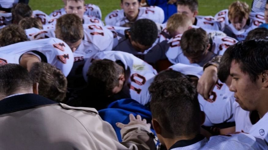 Coach Kennedy Prays after the game with other coaches and players.