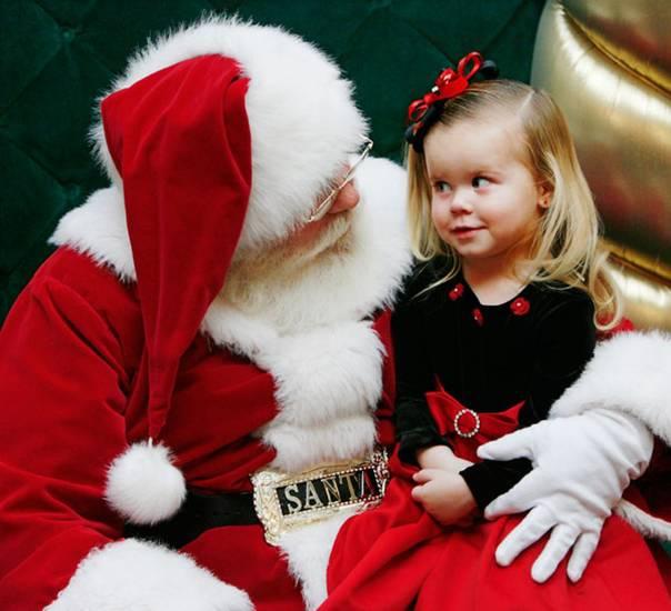 Little girl telling Santa what she wants for Christmas.