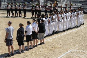Normal West girls' softball team and coaching staff join their opponents for the playing of the National Anthem.