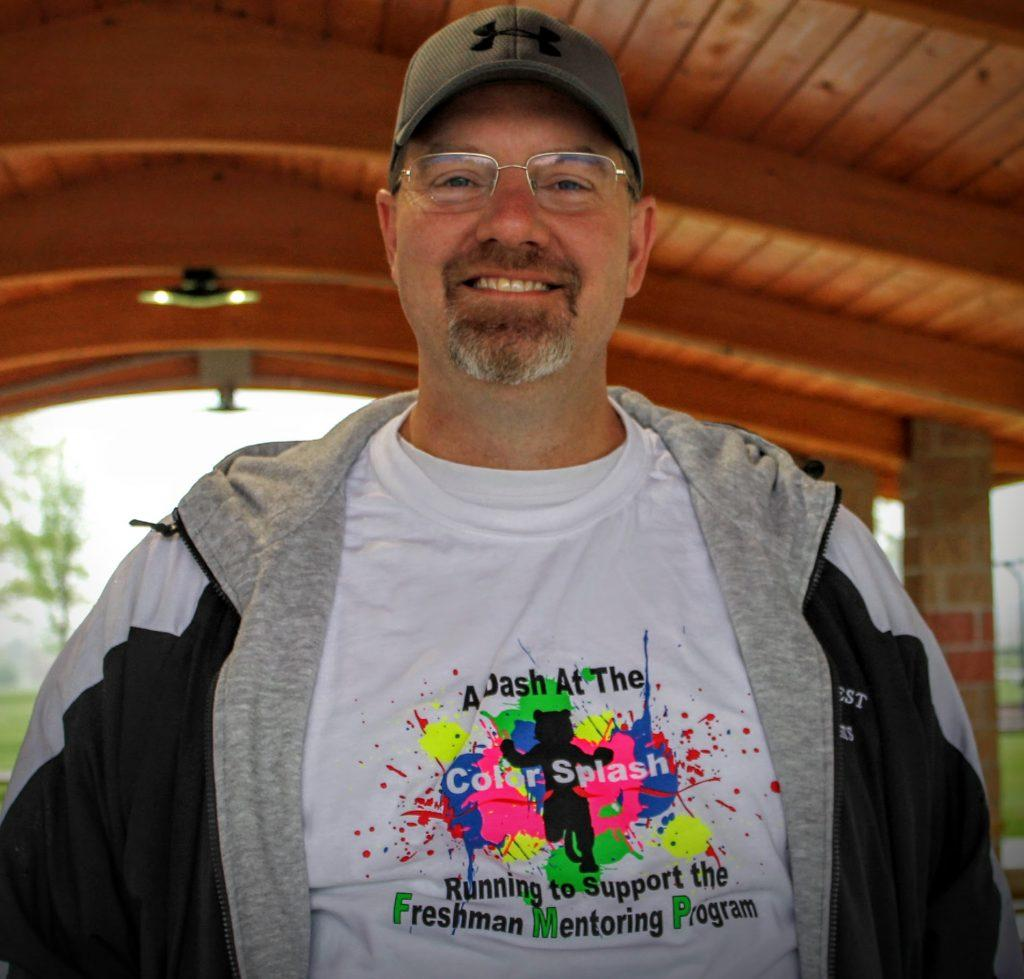 NCWHS principal, Dave Johnson smiles for a photo at the FMP Color Splash 5K.