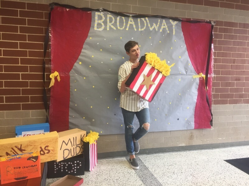 Keaton Knuth strikes a pose next to the decorated photo booth in the junior hall.